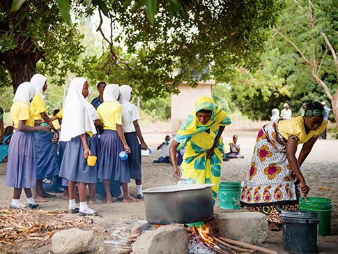 Mother Support Group members in Tanzania prepare uji for school children