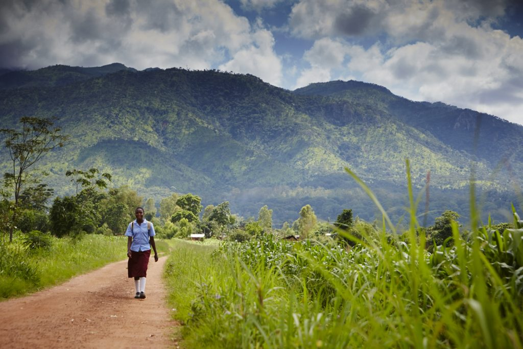 Likwenu, a school girl in uniform, walks along a path with mountains in the background of the image