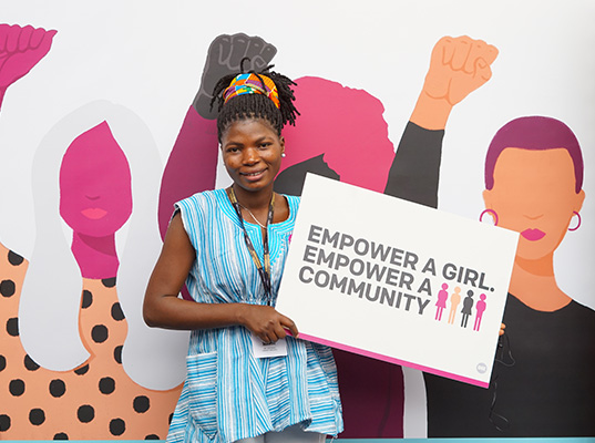Dorcas with 'Empower a girl, empower a community' placard