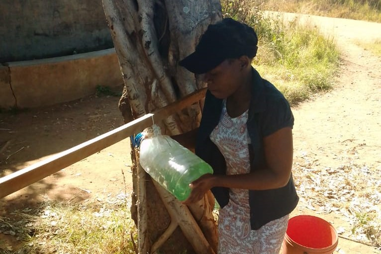 Juliet installs soap at borehole in Zimbabwe
