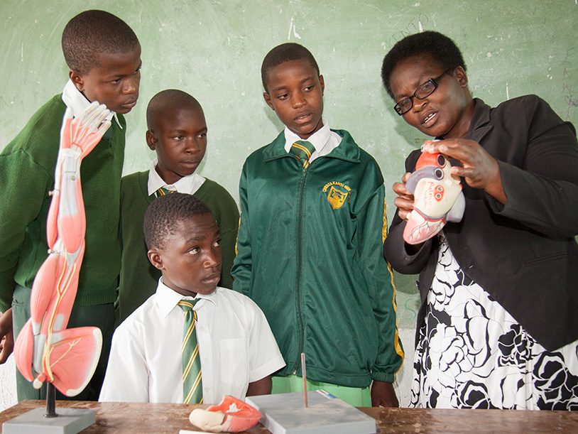 Lameck's student group with his biology teacher and a model of organs