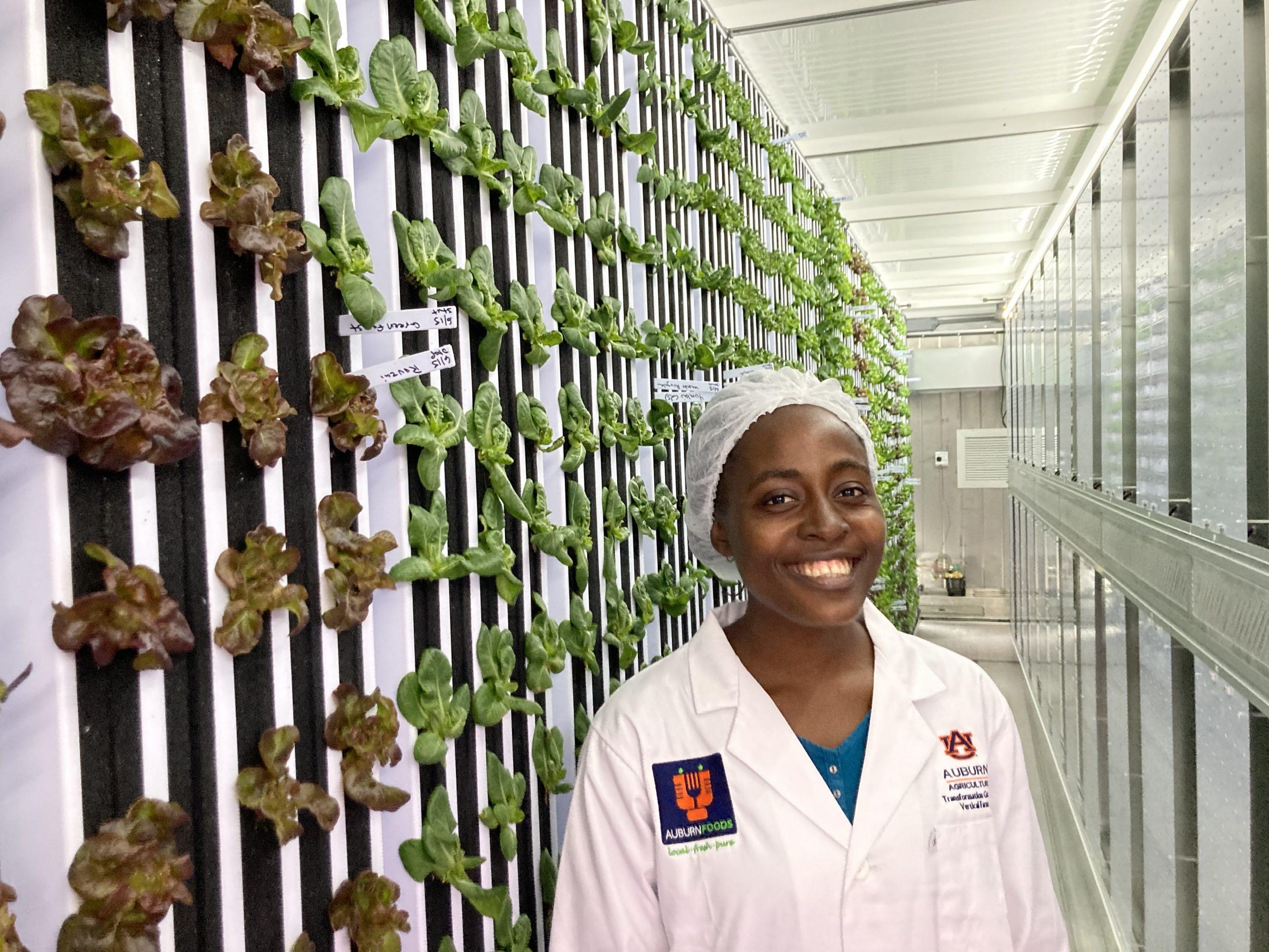 Dorcas Lukwesa with a vertical aquaponics system
