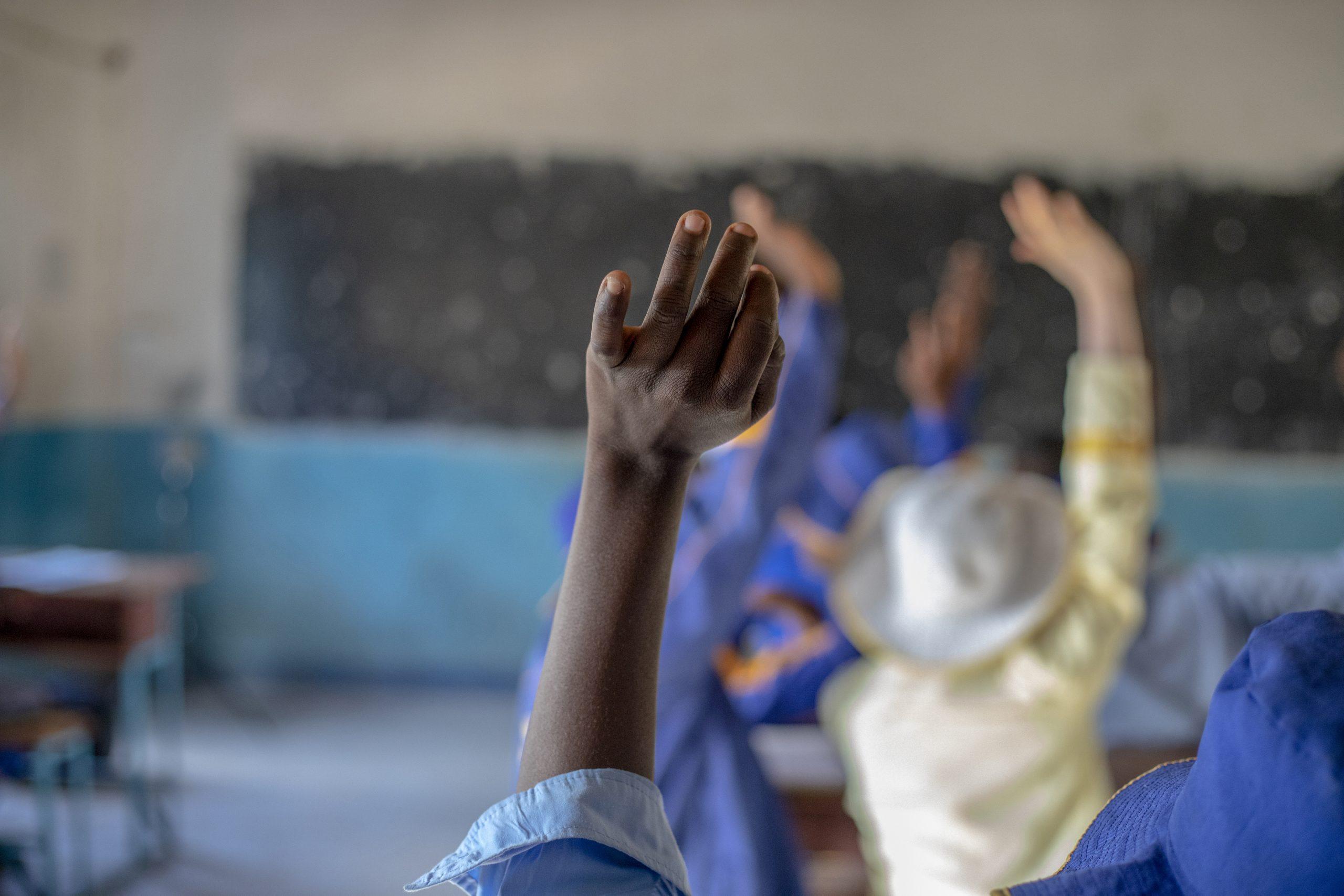 Students raise their hands in class in Kwekwe, Zimbabwe.
