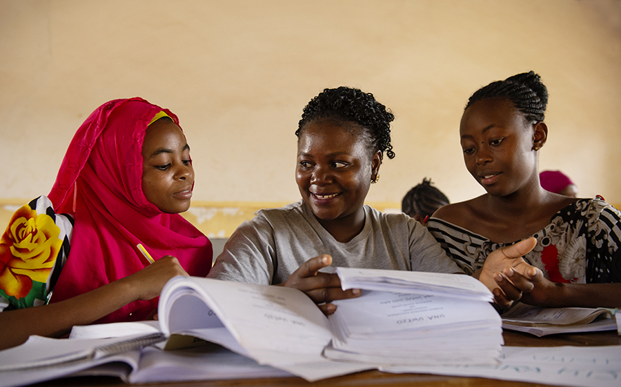 CAMFED Association members and Learner Guides Subira, Stumai, and Hilda check through By Better World exercise books