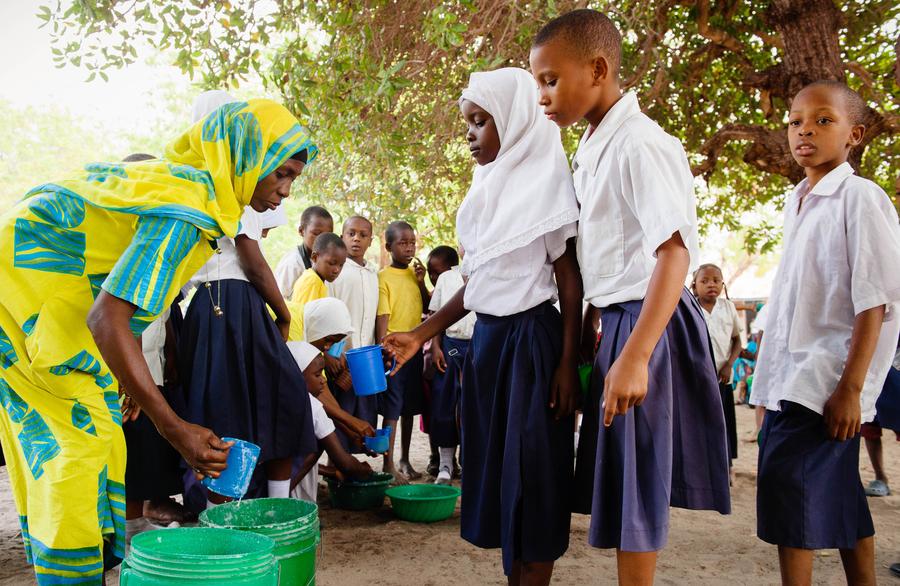 Mwanaidi serves uji to primary students